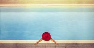帽子的年轻女性在水池 免版税库存图片