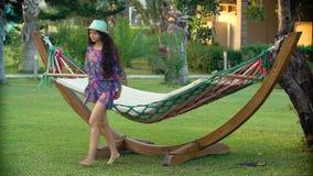 帽子的年轻微笑的深色的妇女放松了和摇摆在热带海滩的吊床 影视素材