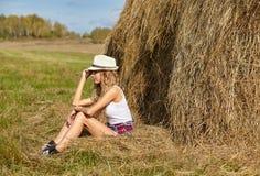 帽子的年轻白肤金发的国家女孩在干草堆附近 免版税库存图片
