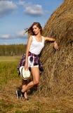 帽子的年轻白肤金发的国家女孩在干草堆附近 库存照片