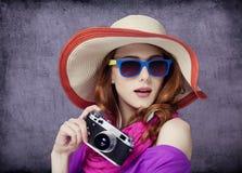 帽子的滑稽的红头发人在背景的女孩有照相机的和bokeh 库存照片