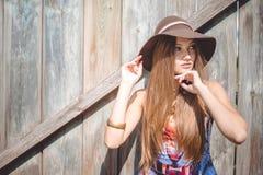 帽子的年轻美丽的妇女和老虎打印上面 库存图片