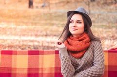 帽子的年轻美丽的妇女坐一条长凳在秋天公园 免版税图库摄影