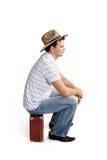 帽子的年轻人坐手提箱 库存照片