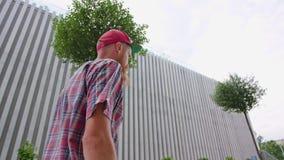 帽子的年轻Readhead行家走街道 股票视频