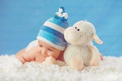 帽子的Cmile婴孩,拥抱在一条白色床罩的玩具,在蓝色b 库存照片
