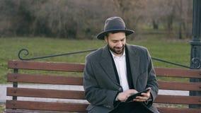 帽子的Hipser创造性的商人使用片剂个人计算机计算机和坐城市街道长凳在断裂期间的公园 免版税库存图片