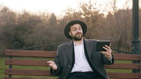 帽子的Hipser创造性的商人使用网上录影闲谈的片剂计算机和坐城市街道长凳在公园 库存图片