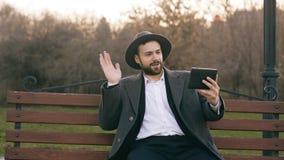 帽子的Hipser创造性的商人使用网上录影闲谈的片剂计算机和坐城市街道长凳在公园 免版税库存图片