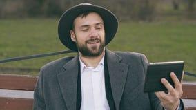 帽子的Hipser创造性的商人使用网上录影闲谈的片剂计算机和坐城市街道长凳在公园 影视素材