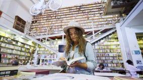 帽子观看的书的女孩在书店里面的手上 影视素材