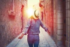 帽子跳舞的妇女在地中海狭窄的街道上 库存图片