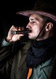 帽子饮用的酒精的牛仔从烧瓶 免版税库存照片