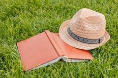 帽子,书,在草的笔记本 免版税库存图片
