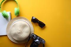 帽子,照相机,太阳镜,耳机,在黄色背景的音乐 免版税库存图片