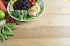 干净的在木桌上的食物顶视图在盘上有菜和鸡 库存图片
