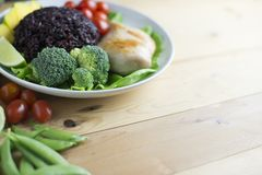 干净的在木桌上的食物顶视图在盘上有菜和鸡 免版税库存图片