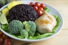 干净的在木桌上的食物顶视图在盘上有菜和鸡 图库摄影