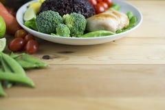 干净的在木桌上的食物顶视图在盘上有菜和鸡 库存照片