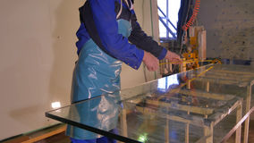 干净的工作者和烘干在制造的玻璃 微笑的中间成人工作者清洁用肥皂擦洗在玻璃窗的sud与橡皮刮板 库存照片