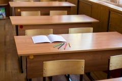 干净的笔记本和色的铅笔在书桌上在空的教室 学校教育的概念 免版税库存照片