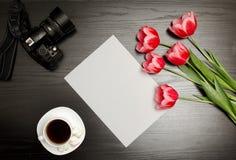 干净的纸片、桃红色郁金香、照相机和一个杯子咖啡 黑色表 顶视图 图库摄影