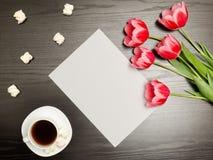 干净的纸片、桃红色郁金香和一个杯子咖啡 黑色表 顶视图 免版税库存照片