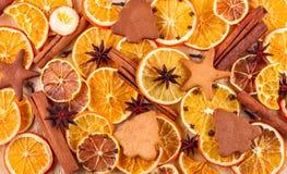 干切片桔子、柠檬、八角、肉桂条和姜饼在米黄背景 库存图片