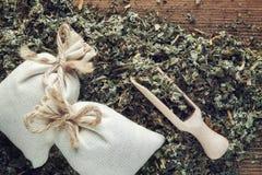 干医药草本背景,两个香囊袋子芳香健康草本和木瓢 免版税图库摄影