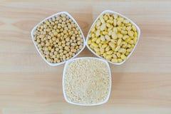 干大豆、被浸泡的大豆和烤地面大豆豆粉粉末在白色碗 图库摄影