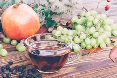从干山楂树莓果的饮料,一束白葡萄和在表特写镜头的一个石榴 库存图片