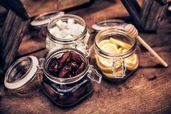 干旱时期、cuted柠檬、糖在玻璃食盒和蜂蜜棍子茶的在木葡萄酒咖啡桌上 库存图片
