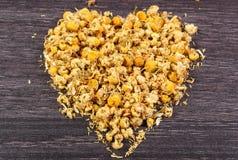 干春黄菊的心脏在木桌,替代医学上的 库存图片