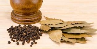 干月桂叶和黑胡椒在木背景 库存图片
