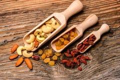 干果子和坚果在匙子在自然木头 免版税库存图片