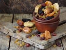 从干果子-日期,无花果,杏子,修剪,葡萄干, cranberrie不同的品种的构成在木背景的 图库摄影