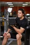 干涉在黑sportwear的男性与在健身房的哑铃一起使用反对镜子 免版税库存图片