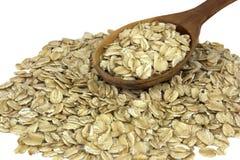 干燕麦在与木匙子的白色背景剥落 免版税库存图片