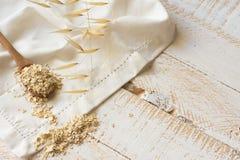 干燕麦粥在一块白色亚麻布,植物枝杈的一把wooen匙子剥落 库存照片