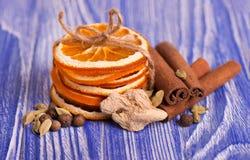 干燥切片桔子、桂香、多香果和豆蔻果实,在蓝色木背景 芳香香料 圣诞节 库存图片