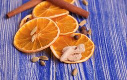 干燥切片桔子、桂香、姜和豆蔻果实,在蓝色木背景 芳香香料 圣诞节装饰生态学木 库存图片
