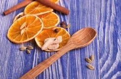 干燥切片桔子、桂香、姜和豆蔻果实,在蓝色木背景 芳香香料 圣诞节装饰生态学木 免版税库存图片