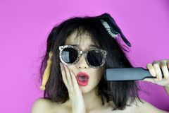 干燥和损坏的头发,掉头发由称呼工具直挺器的热头发的问题原因,滑稽的女孩和坏头发天 免版税库存照片