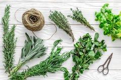 干燥新鲜的草本和绿叶香料食物的在白色木厨房书桌背景顶视图样式 免版税库存照片