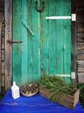 干燥杉木锥体、房子灯笼和杉树装饰在年迈的被风化的木门背景的一个木箱分支与horsesh 免版税图库摄影