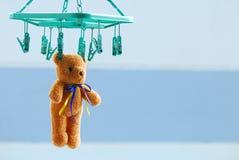 干燥棕色玩具熊垂悬与室外的钳位 免版税库存照片