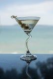 干燥马蒂尼鸡尾酒有海景背景 免版税库存照片