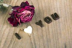 干玫瑰色和巧克力词我爱你 库存照片