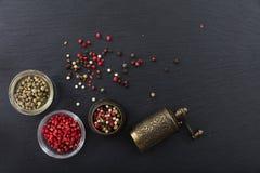 干胡椒和一个古铜色胡椒磨在黑背景,顶视图,拷贝空间 库存照片