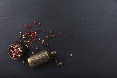 干胡椒和一个古铜色胡椒磨在黑背景,顶视图,拷贝空间 库存图片